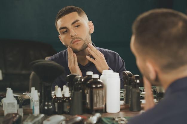 Styl, aby zaimponować. horyzontalny strzał młody człowiek sprawdza jego przyciętą brodę patrzeje lustro