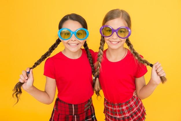 Styl imprezowy. szkolna impreza balowa. czerwone dziewczyny mody. szczęśliwe dziewczynki w kraciastej spódnicy. stylowe dzieci w mundurkach szkolnych. małe dziewczynki w fantazyjnych okularach. śmieszne dzieci w okularach przeciwsłonecznych. wakacje letnie.