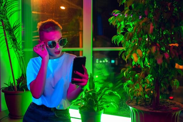 Styl. kinowy portret stylowej kobiety w oświetlonym neonem wnętrzu. stonowane jak efekty kinowe, jasne neonowane kolory. kaukaski model za pomocą smartfona w kolorowe światła w pomieszczeniu. kultura młodzieżowa.