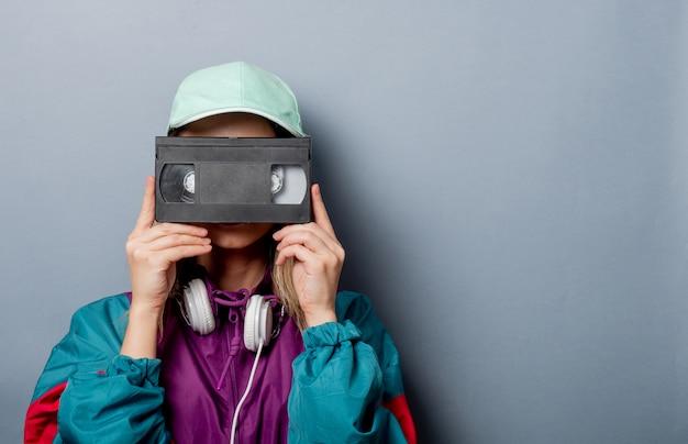 Styl kobiety w stylu lat 90. z kasetą wideo vhs