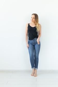 Styl, koncepcja ludzi - młoda kobieta w dżinsach i czarnej koszuli stojąca nad białą ścianą