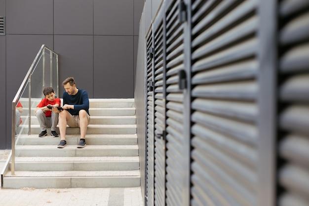 Styl miejskiego życia współczesnej rodziny. widok miejski, tata i syn siedzą na betonowych schodach i spędzają razem czas