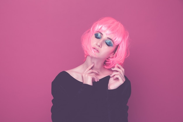 Styl pop kobieta w różowej peruce i czarnych ubraniach pozowanie na aparat na białym tle.