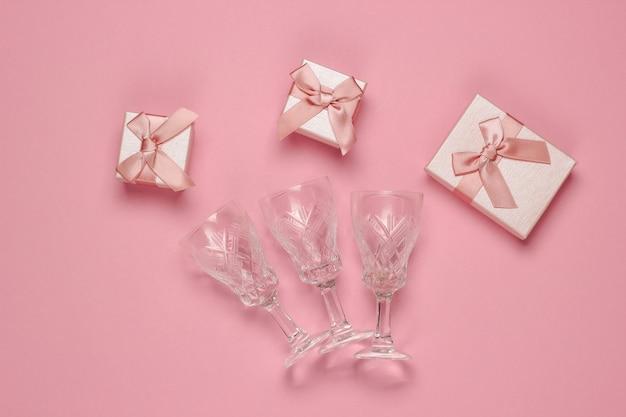 Styl retro fasetowane kryształowe kieliszki do wina i pudełka na różowym tle. koncepcja bożego narodzenia. widok z góry