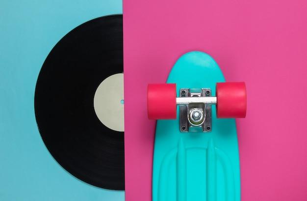 Styl retro. plastikowa mini cruiser oraz płyta winylowa na kolorowym tle. trend w pastelowych kolorach. letnia zabawa. minimalistyczna koncepcja młodzieży.