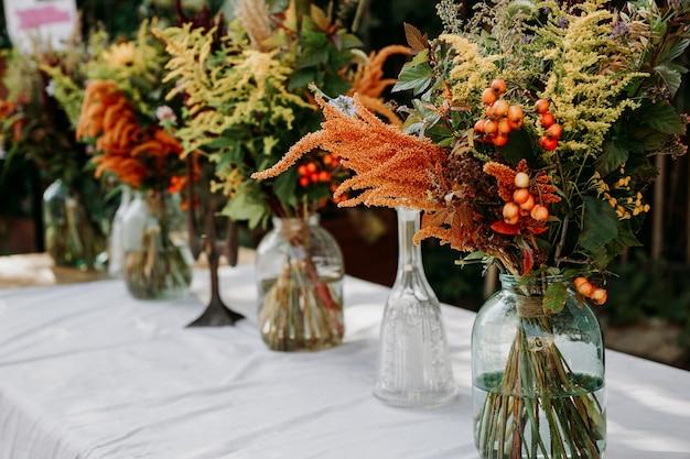 Styl rustykalny. bukiety w stylu boho na stole w szklanych wazonach i słoikach. drewniany stół i biały obrus