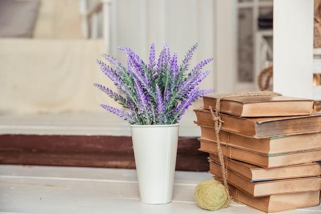 Styl shabby chic. dekoracja z klasycznymi książkami i lawendą. shabby elegancki wystrój wnętrz domu wiejskiego. lawenda w dzbanku, książki. dekoracja domu.