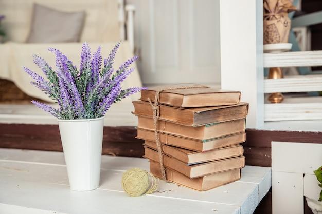 Styl shabby chic. dekoracja z rocznika książek i lawendy. wystrój wnętrz domu wiejskiego. lawenda w dzbanku, książki. dekoracja domu.