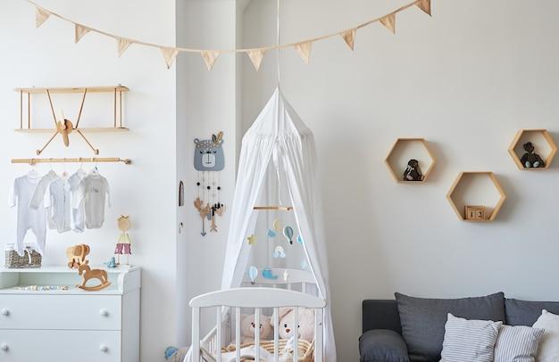 Styl skandynawski białe wnętrze pokoju dziecięcego, sypialni, pokoju dziecinnego. łóżeczko dziecięce z baldachimem. drewniane półki i zabawki. drewniana półka w formie samolotu
