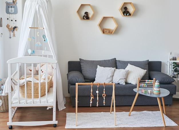 Styl skandynawski białe wnętrze pokoju dziecięcego, sypialni, pokoju dziecinnego. łóżeczko dziecięce z baldachimem. drewniane półki i zabawki. symulator rozwojowy dla dzieci.