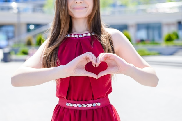 Styl stylowy piękna pani wakacje uczucia emocje koncepcja. przycięte zdjęcie z bliska portret zabawy radość radosna podekscytowana wesoła dziewczyna robiąca serce na klatce piersiowej za pomocą palców w tle ulicy miasta
