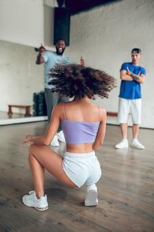 Styl, taniec. dziewczyna w szortach i tenisówkach z plecami pięknie kucająca w tańcu i jej przyjaciele