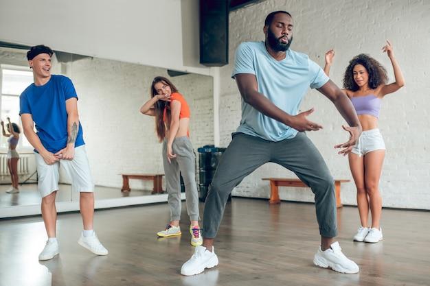 Styl, taniec. tańczący skupiony brodaty afroamerykanin i uważny, radosny młody człowiek w pomieszczeniu