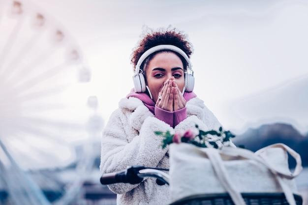 Styl uliczny. piękna międzynarodowa kobieta zakrywająca usta podczas spaceru po ulicy