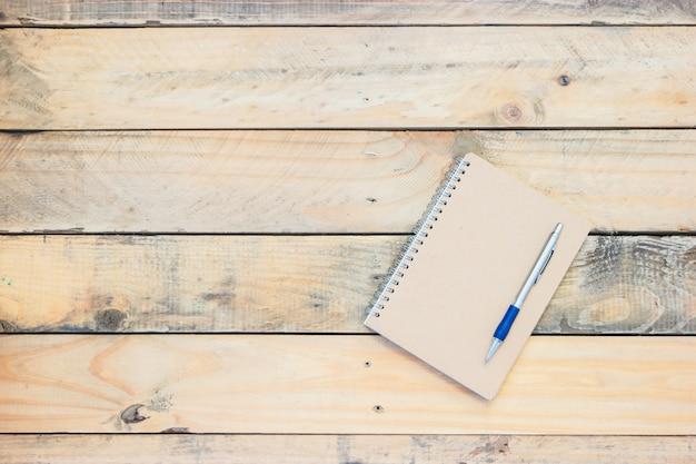Styl vintage notatnik i długopis na starej drewnianej podłodze.