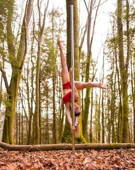 Styl życia blond akrobaty kaukaskiej tańczącej w czerwonym kostiumie do tańca na rurze w lesie jesienią do góry nogami
