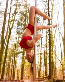 Styl życia blond akrobaty kaukaskiej tańczącej w lesie jesienią w czerwonym stroju do tańca na rurze