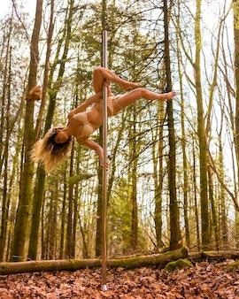 Styl życia blond kobiety rasy kaukaskiej taniec taniec na rurze w lesie jesienią akrobacje w naturze z przenośnym słupem