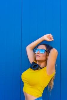 Styl życia, blondynka kaukaska z żółtą koszulką. młoda kobieta pozuje z muzyką słuchawki i okulary przeciwsłoneczne