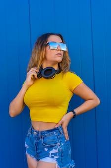 Styl życia, blondynka kaukaska z żółtą koszulką. młoda kobieta pozuje z zmysłowym spojrzeniem słuchawki muzyczne i okulary przeciwsłoneczne