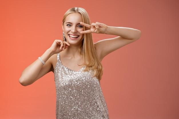 Styl życia. charyzmatyczny, zabawny, rozbawiony, czarująca blond dziewczyna w wieku 25 lat, bawiąca się tańcząc na czerwonym tle w srebrnej modnej błyszczącej sukience na imprezę, pokazująca pokojowy gest dyskotekowy w pobliżu oka uśmiechnięty beztrosko.