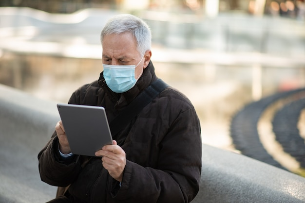 Styl życia covid koronawirusa, zamaskowany starszy biznesmen używający swojego tabletu, siedząc na placu miejskim