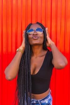 Styl życia czarna dziewczyna z dużym warkoczem w dżinsowych szortach i okularach przeciwsłonecznych na czerwonej ścianie portret młodej tancerki trapowej