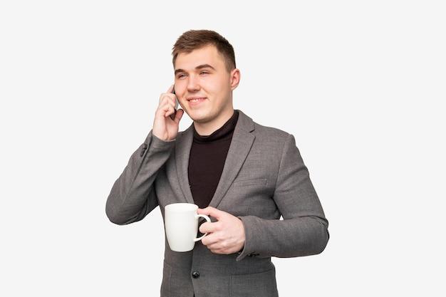 Styl życia człowieka biznesu. profesjonalna komunikacja. wesoły menedżer o kawę telefon na białym tle.