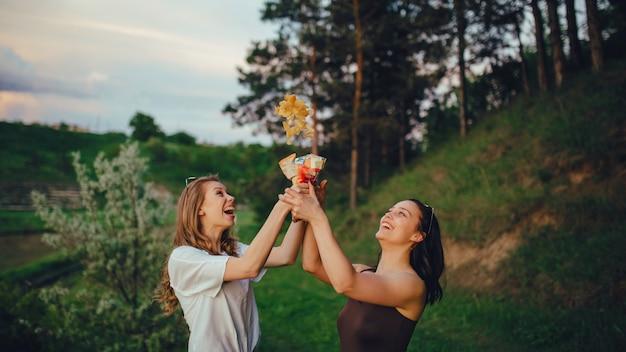 Styl życia. dwie szczęśliwe koleżanki bawią się, rzucają chipsy ziemniaczane, o zachodzie słońca, pozytywny wyraz twarzy, na zewnątrz