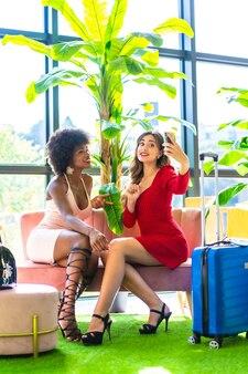 Styl życia, dwoje przyjaciół niedawno przybyło do hotelu z walizkami, kręcąc wideo dla sieci społecznościowych, kaukaska blondynka i czarna dziewczyna z afro włosami, różową i czerwoną sukienką.