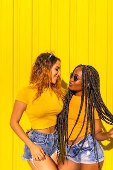 Styl życia dziewczyny, czarna dziewczyna z długimi warkoczami i blondynką w żółtych koszulach i krótkich dżinsach na żółtej ścianie. zabawa w mieście na żółtej ścianie