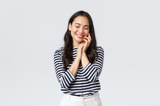 Styl życia, emocje ludzi i dorywcza koncepcja. piękna śliczna azjatycka dziewczyna czuje miękkość skóry po zastosowaniu produktu kosmetycznego, kosmetyków do pielęgnacji skóry, uśmiecha się zachwycona, dba o twarz