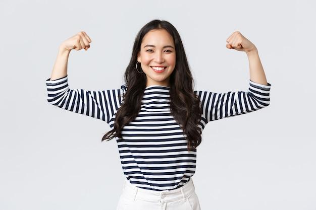 Styl życia, emocje ludzi i dorywcza koncepcja. silna i pewna siebie azjatycka kobieta zgina biceps, chwaląc się swoim idealnym kształtem po zapisaniu się na siłownię, chwaląc się mięśniami, treningiem i uczuciem siły