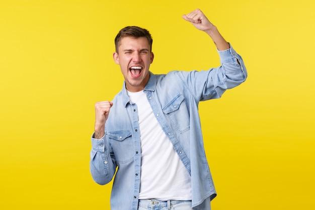 Styl życia, emocje ludzi i koncepcja letniego wypoczynku. entuzjastyczny przystojny szczęśliwy mężczyzna podnoszący ręce do góry, intonujący i krzyczący tak jako wygrywający, triumfujący nad nagrodą na loterii, żółte tło.