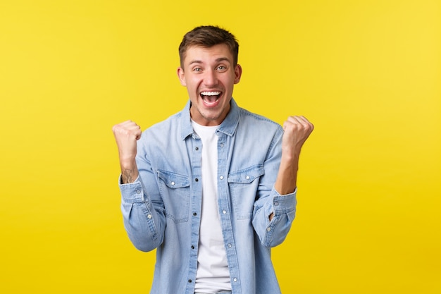 Styl życia, emocje ludzi i koncepcja letniego wypoczynku. podekscytowany przystojny szczęśliwy mężczyzna radujący się, podnoszący ręce do góry i śpiewający, kibicujący drużynie, będąc mistrzem, triumfujący na żółtym tle.