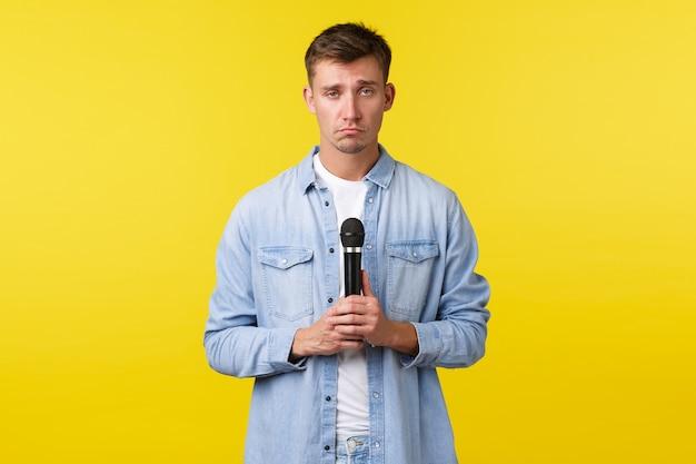 Styl życia, emocje ludzi i koncepcja letniego wypoczynku. ponury smutny blondyn, student z mikrofonem wyglądający na zdenerwowanego, śpiewający łamiącą serce piosenkę, stojący na żółtym tle.