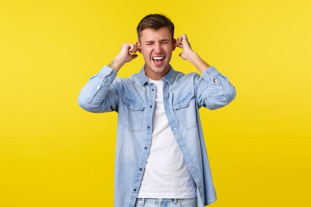 Styl życia, emocje ludzi i koncepcja letniego wypoczynku. przygnębiony i zdenerwowany przystojny student płci męskiej krzyczy wkurzony, zatyka uszy palcami, niechętnie słucha, stoi na żółtym tle.