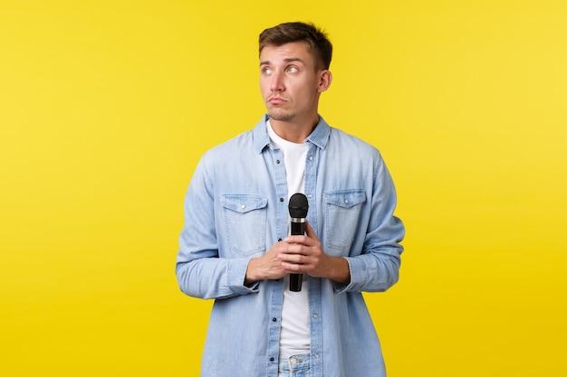 Styl życia, emocje ludzi i koncepcja letniego wypoczynku. rozważny marzycielski przystojny mężczyzna odwracający wzrok, myślący jak trzymający mikrofon, stojący niezdecydowany na żółtym tle