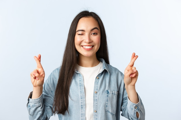 Styl życia, emocje ludzi i koncepcja piękna. nadzieja optymistyczna ładna azjatycka dziewczyna składa życzenie. studentki skrzyżowane palce przed wynikami badań, mrugają i uśmiechają się, modląc się, aby otrzymać dobrą wiadomość.