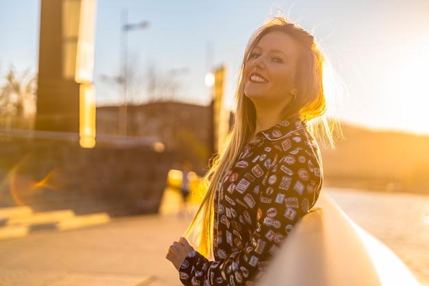 Styl życia, fragment portretu młodej blondynki w mieście bilbao o zachodzie słońca