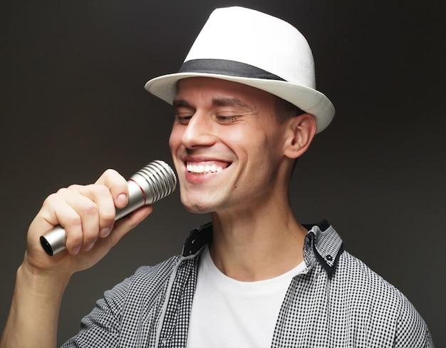 Styl życia i koncepcja ludzi: młody człowiek piosenkarz z mikrofonem