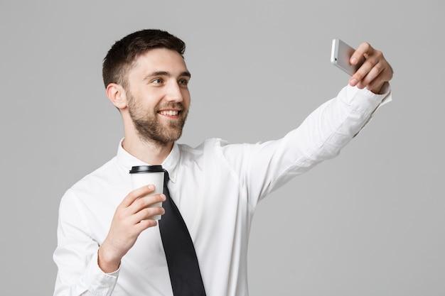 Styl życia i koncepcji biznesowych - portret przystojny biznesmen korzystają biorąc selfie z wyprowadzić filiżankę kawy. izolowane białe tło. skopiuj miejsce.