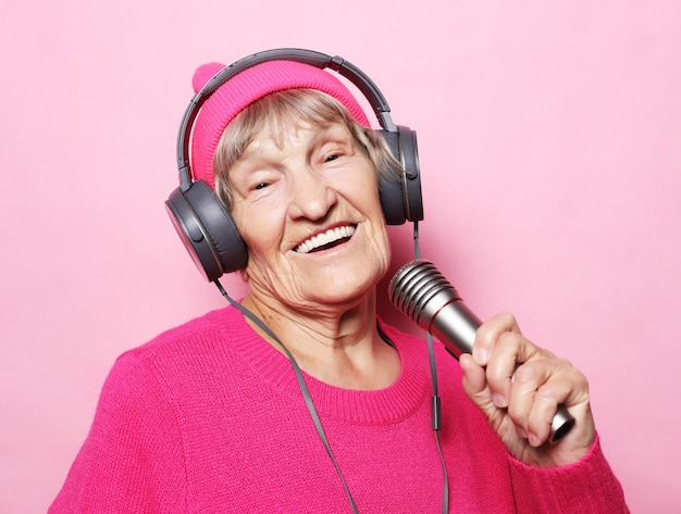 Styl życia i ludzie: zabawna starsza pani słucha muzyki przez słuchawki i śpiewa z mikrofonem
