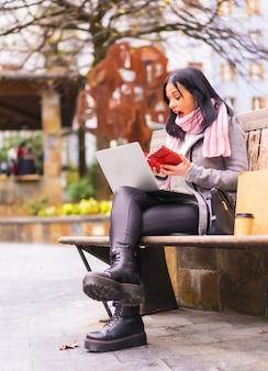 Styl życia, kaukaska brunetka dziewczyna otwierająca prezent od chłopaka na rozmowie wideo, oddzielona odległością