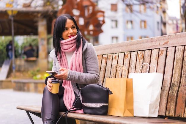 Styl życia, kaukaska brunetka robi zakupy w mieście z papierowymi torbami i kawą na wynos, siedząca i wysyłająca wiadomość przez telefon