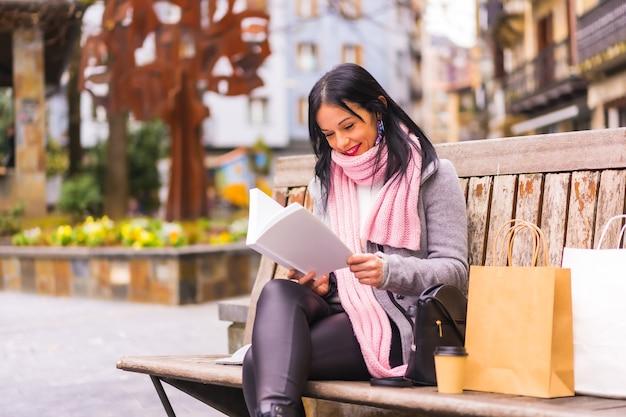 Styl życia, kaukaski brunetka dziewczyna czytając książkę w parku miejskim, uśmiechając się siedząc na ławce