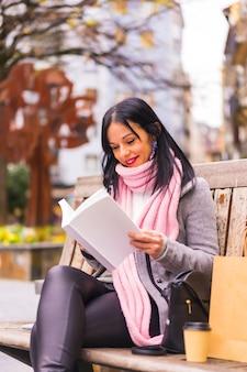 Styl życia, kaukaski brunetka dziewczyna czytając książkę w parku, uśmiechając się siedząc na ławce