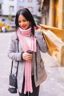 Styl życia kaukaskiej brunetki na zakupy w mieście z papierowymi torbami i kawą na wynos