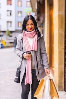 Styl życia kaukaskiej brunetki robiącej zakupy w mieście z papierowymi torbami i kawą na wynos, pionowe zdjęcie