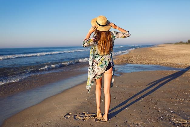 Styl życia lato moda portret piękna blondynka pozuje na samotnej plaży, ubrana w bikini stylowe pareo i kapelusz, spojrzenie na ocean, nastrój luksusowych wakacji, jasne stonowane kolory.
